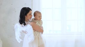 Mooie moeder met haar peuter en pasgeboren zonen die engelenkostuums dragen stock videobeelden
