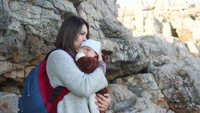 Mooie moeder met rugzak die en schreeuwende babyjongen kalmeren koesteren stock videobeelden