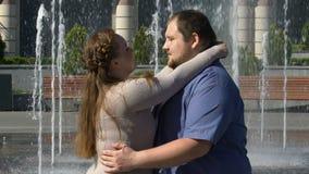 Mooie mollige vrouw die teder haar zwaarlijvige vriend, openluchtdatum langzaam-mo koesteren stock footage