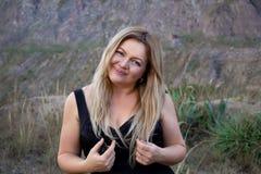 Mooie mollige vrouw in een zwarte kleding Blonde Met een mooie glimlach In openlucht op een prairie stock afbeeldingen