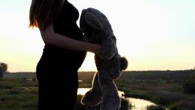 Mooie monet - jong zwanger meisjesspel met beer bij zonsondergang stock videobeelden