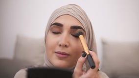 Mooie moslimvrouw die make-up op haar gezicht met borstel doen, die oogschaduw op haar ooglid toepassen Het dragen van beige hija stock video