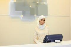 Mooie Moslimvrouw die zich achter de ontvangst in het hotel bevinden stock fotografie