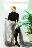 Mooie naaister die, die op een stoel zitten en de grijze stof houden stock afbeelding