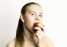 Mooie naakte jonge vrouw die een appel eten gezond voedsel - sterk tandenconcept Stock Afbeelding