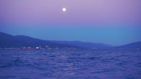 Mooie nacht en volle maan over havenstad, schepen in de afstand stock footage