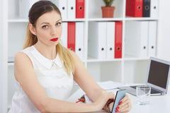 Mooie nadenkende bedrijfsvrouwenzitting die op het bureauwerk mobiele telefoon houden Royalty-vrije Stock Fotografie