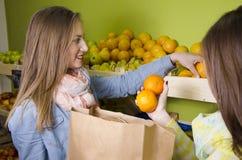 Mooie natuurlijke brunettes die sinaasappelen kopen royalty-vrije stock foto's