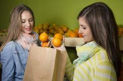 Mooie natuurlijke meisjes die sinaasappelen kopen stock fotografie