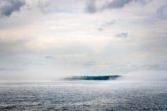 Mooie noordse die de zomermening van de archipel van een eiland door dikke nevel en mist bij de horizon wordt omringd royalty-vrije stock afbeeldingen