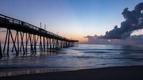 Mooie oceaanzonsopgang en zachte golven naast een oude houten visserijpijler die zich veel uit in het overzees uitbreiden stock afbeelding