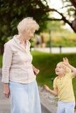 Mooie oma en haar weinig kleinkind die samen lopen stock foto's