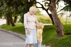 Mooie oma en haar weinig kleinkind die samen in park lopen royalty-vrije stock afbeeldingen