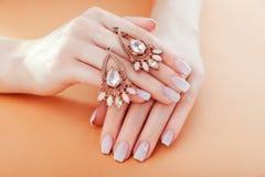 Mooie ombremanicure met oorringen Frans spijkerontwerp De juwelen van de vrouwenholding Het concept van de manier royalty-vrije stock afbeelding
