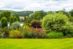 Mooie ommuurde, victorian tuin met verscheidenheid van bloemen en bomen stock fotografie