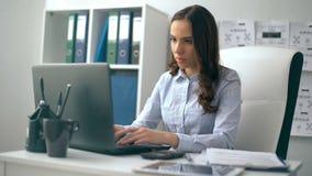 Mooie onderneemster die aan haar laptop werken terwijl het zitten op kantoor stock footage