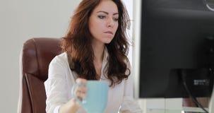 Mooie onderneemster die in bureau het drinken koffie werken stock videobeelden