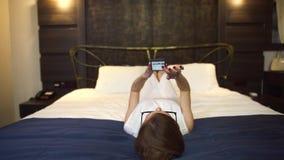 Mooie onderneemster die in glazen op telefoon van de bed de texting cel leggen stock videobeelden