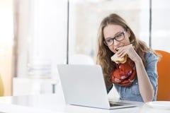 Mooie onderneemster die sandwich eten terwijl het gebruiken van laptop in bureau royalty-vrije stock afbeeldingen