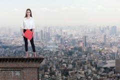 Mooie onderneemster die zich op het dak van een wolkenkrabber over een stad bevinden stock afbeeldingen