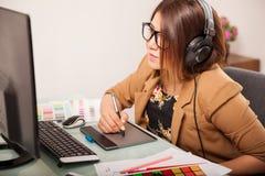 Mooie ontwerper die aan muziek luisteren Stock Afbeeldingen