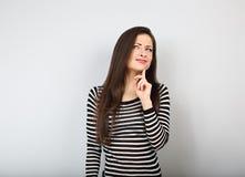 Mooie onzekere vrouw met vinger onder het gezicht die en omhoog in toevallig overhemd en lang haar denken kijken stock fotografie