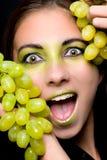 Mooie opgewekte vrouw die groene druiven houdt royalty-vrije stock fotografie