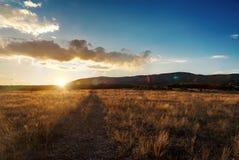 Mooie oranje de herfstzonsondergang op droog grasgebied met weg Bergachtergrond Royalty-vrije Stock Afbeeldingen