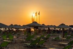 Mooie oranje en gele zonsondergangmening die met mensen in sunchairs bij een strand liggen stock afbeeldingen