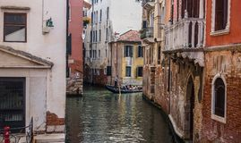 Mooie oude Venetiaanse straat met oude sjofele kleurrijke gebouwen en toeristen in gondel stock fotografie