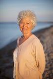 Mooie oude vrouw die zich alleen bij het strand bevinden Stock Foto