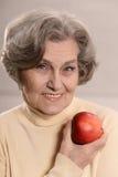 Mooie oude vrouw met een appel Stock Fotografie