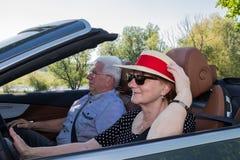 Mooie oudere vrouw met zonhoed en haar partner in een auto stock foto's