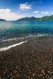 Mooie overzees en zwart kiezelsteenstrand bij tropisch eiland Royalty-vrije Stock Afbeelding