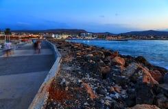 Mooie overzees met avond zacht licht van de zonsondergang tegen bewolkte hemel met kustlijn met stenen en promenadeweg royalty-vrije stock afbeeldingen