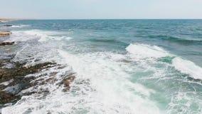 Mooie overzeese golven Luchtschot, die over de rollende golven vliegen die op de rotsen breken stock video