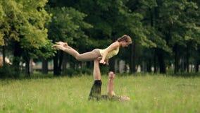 Mooie paar het praktizeren acroyoga De jonge praktijk van yogainstructeurs in een stadspark op groen gras Succesvolle twee stock footage