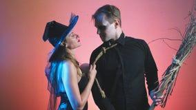 Mooie paar, man en vrouw in kostuums van heksen en zombieën op Halloween, 4k die, slow-motion, een bezem houden stock footage