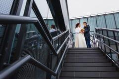 Mooie paarjonggehuwden op een metaaltrap Stock Afbeelding