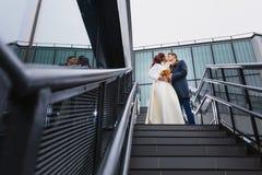 Mooie paarjonggehuwden op een metaaltrap Royalty-vrije Stock Foto