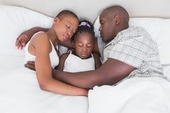 Mooie paarslaap met hun dochter in hun bed Stock Foto's