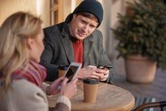 Mooie paarzitting bij koffie met mobiles stock fotografie