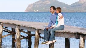 Mooie paarzitting op de pier die van de dag genieten stock video