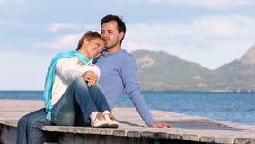 Mooie paarzitting op de pier die van het overzees genieten stock footage