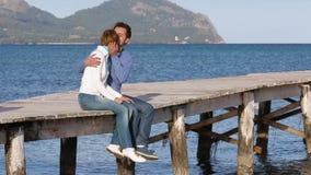 Mooie paarzitting op de pier die van hun tijd genieten stock video