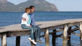 Mooie paarzitting op de pier die van tijd samen genieten stock footage