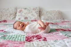 Mooie pasgeboren babyjongen, wijd glimlachen, verpakt in omslag, lyi Stock Foto's