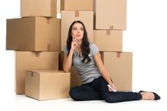 Mooie peinzende vrouw tijdens beweging met dozen bij nieuwe vlakte Royalty-vrije Stock Foto's