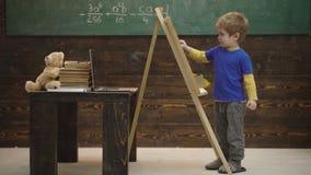 Mooie peuterjongen die op bord op houten achtergrond trekken Kleine kunstenaarsverven op een houten achtergrond Concept van stock footage
