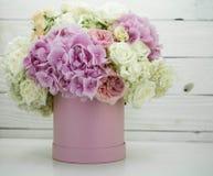 Mooie pioenen in de roze doos met vruchten op houten achtergrond Stock Afbeeldingen